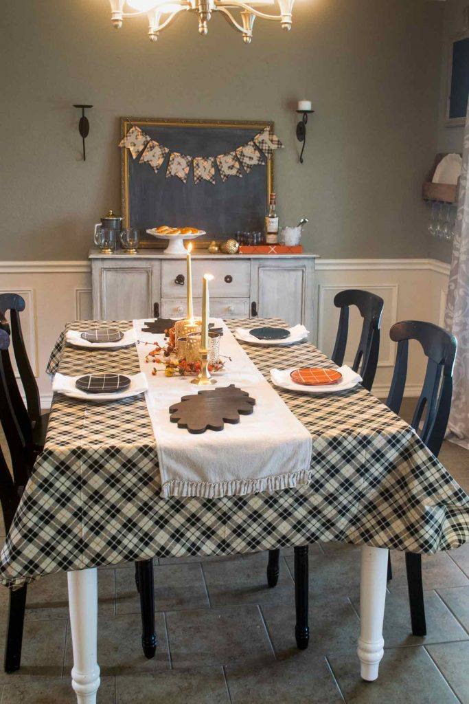 a dining room table set for fall with a plaid tablecloth, stained wooden leaf chargers, and a gilded centerpiece