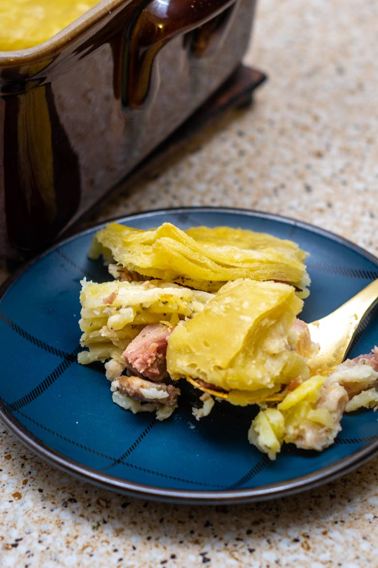blue plaid plate next to a brown casserole dish with scalloped potato pie with ham