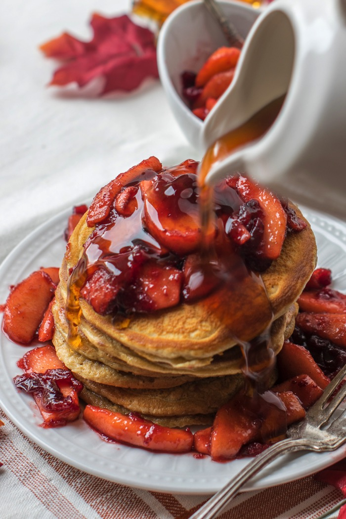 Maple syrup over cranberry and apple topped gingerbread pancakes.