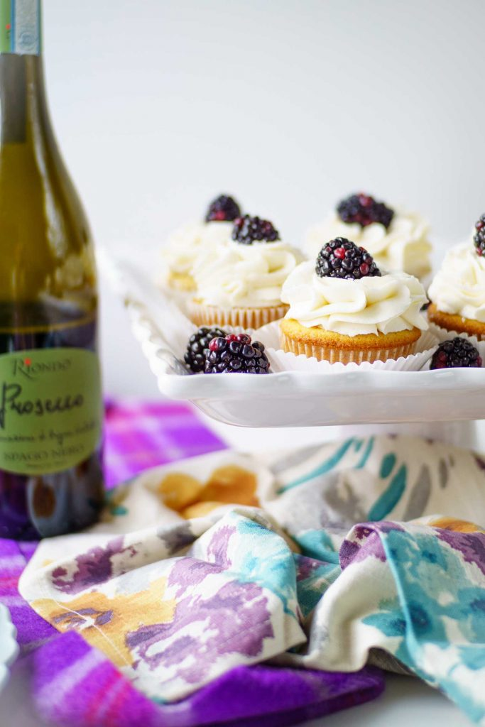 Prosecco cupcakes with prosecco frosting topped with a blackberry