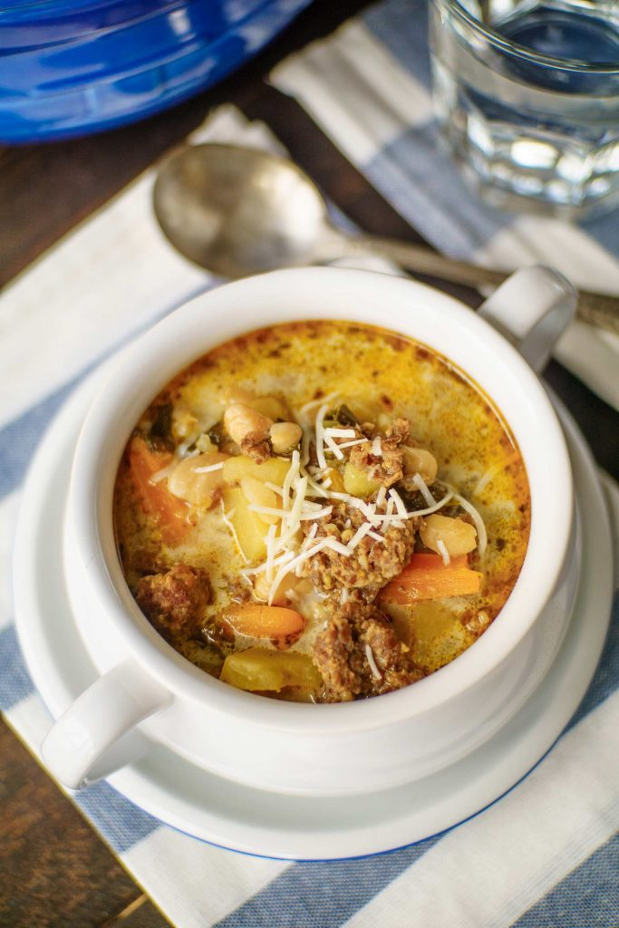 Kale white bean and sausage soup topped with parmesan