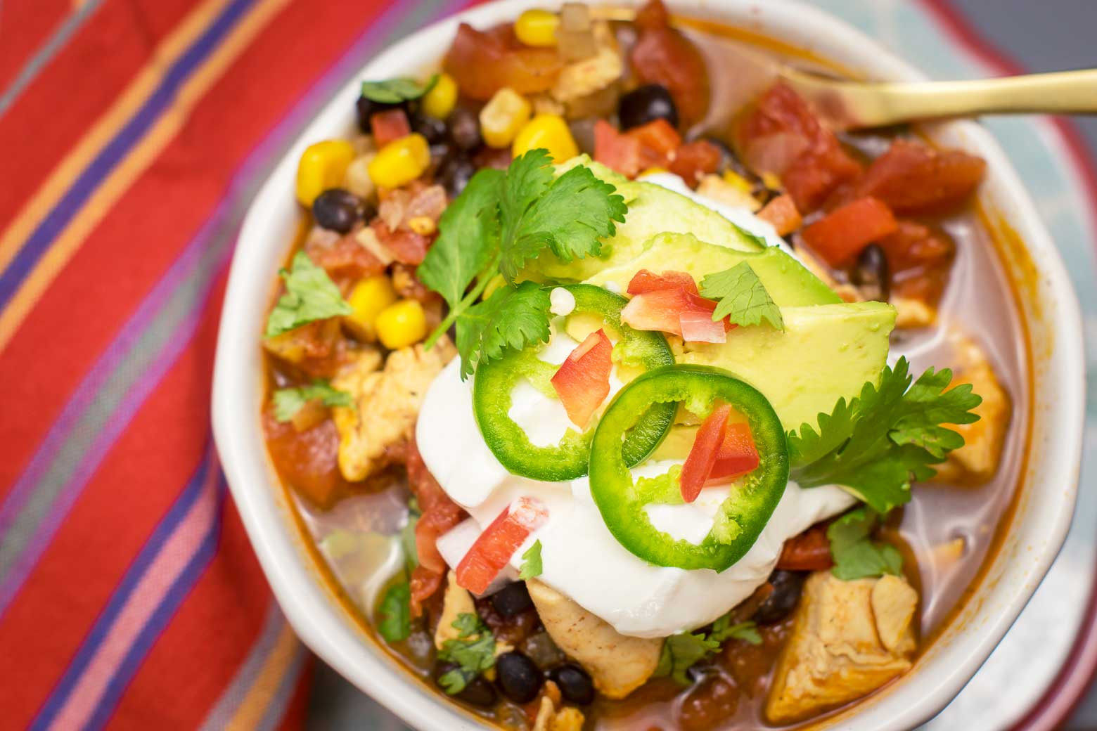 Chicken chili topped with sour cream, fresh cilantro, jalapeños, red peppers, and avocado.