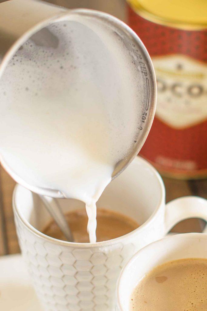 adding steamed milk to latte