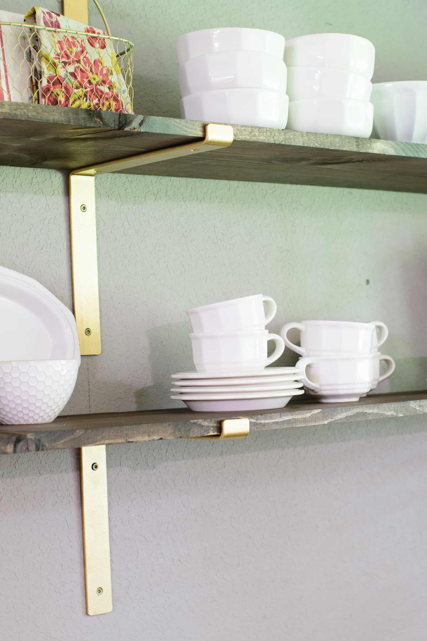 white teacups and bowls on wood shelves with gold brackets