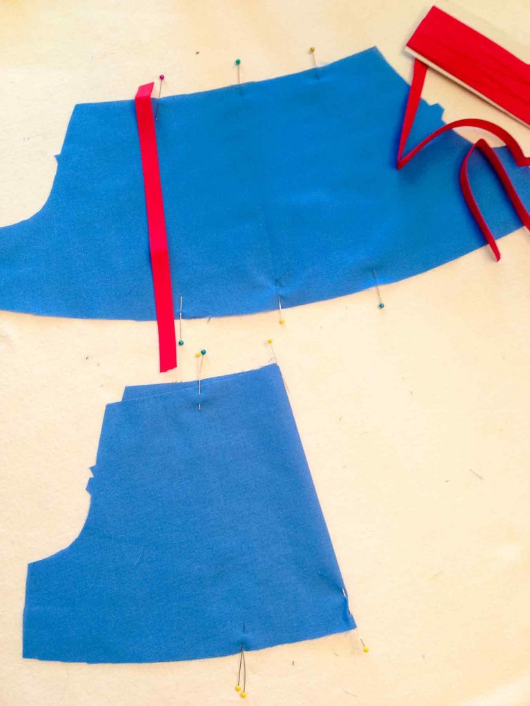 Adding trim to snow white costume sleeves : Up close view of red stripe detail on Snow White peasant dress sleeve before sewing