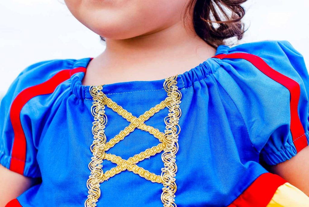 Up close view of gold ribbon detail on Snow White peasant dress for a little girl