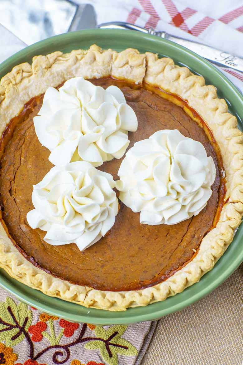 pumpkin pie recipe with molasses flavoring topped with whipped cream flowers