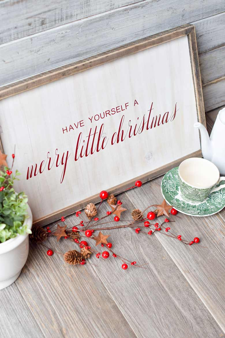 Christmas display with a vinyl christmas sign, teapot and teacup and holiday greenery