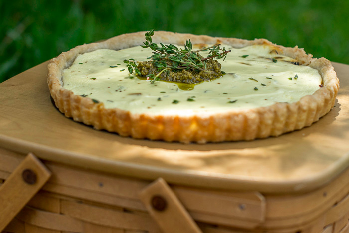 caramelised balsamic onion and goat cheese tart on a picnic basket topped with pesto and thyme