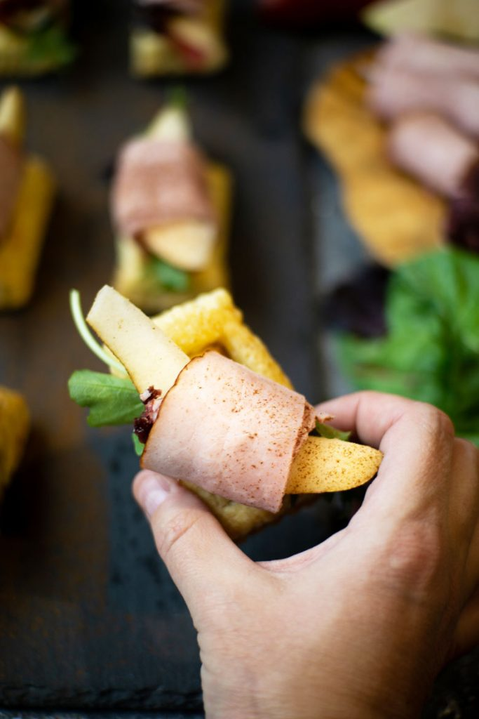 easy handheld appetizers made from puff pastry, meat, fruit and goat cheese