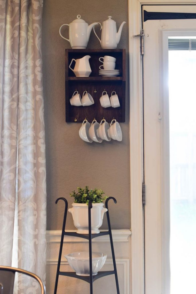Tea pots on a shelf designed to hold mugs and cups from hooks for easy kitchen storage