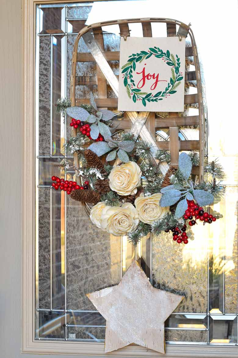 Christmas Front Door Wreath made from a basket, roses, evergreen and berry picks and more!