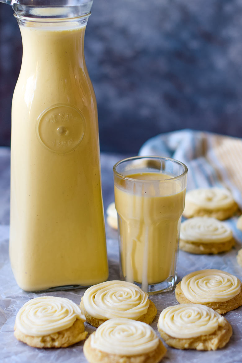Eggnog sugar cookies with a piped eggnog frosting sitting next to a jug of real egg nog