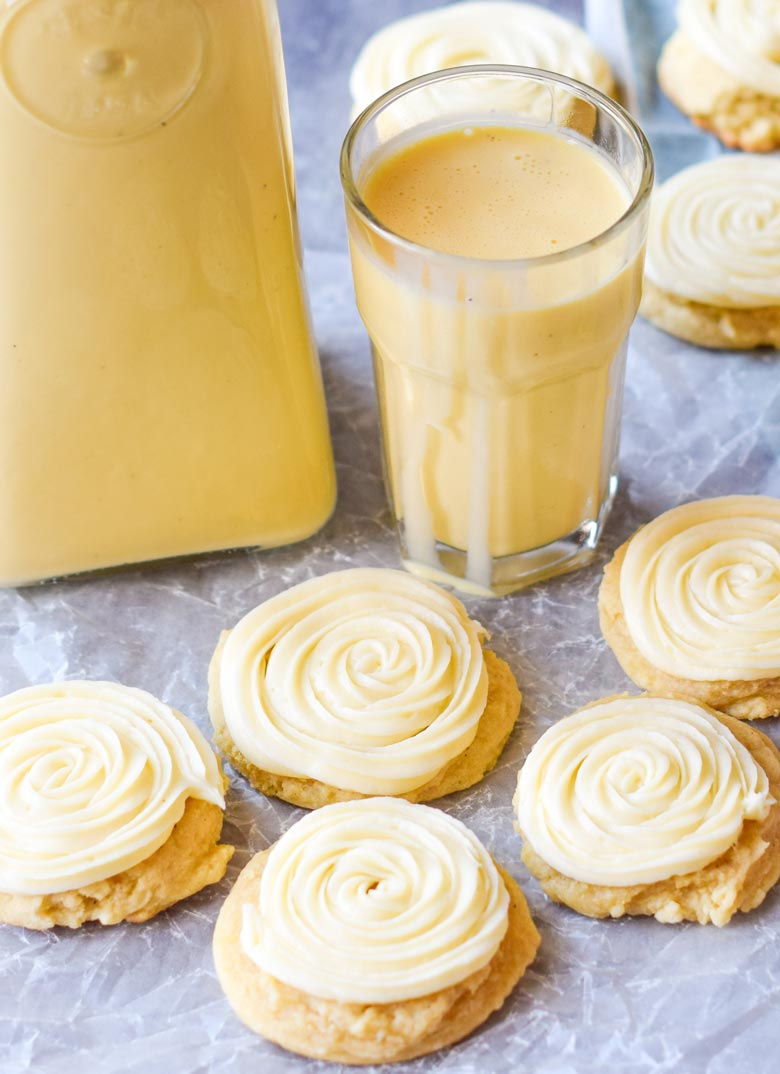 Eggnog cookies with a spiced sugar cookie dough and elegantly piped eggnog frosting next to a pitcher and glass of eggnog