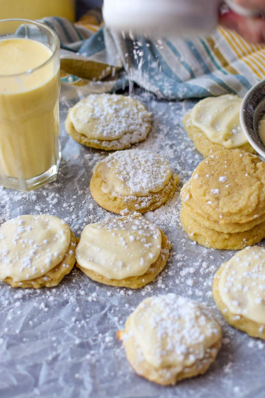sprinkling powdered sugar on an iced eggnog sugar cookie with eggnog buttercream icing.