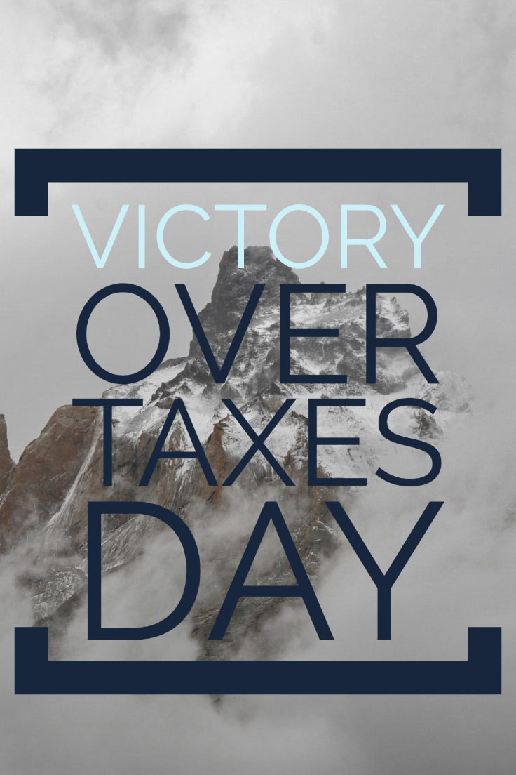 Mountain in clouds with the words victory over taxes day