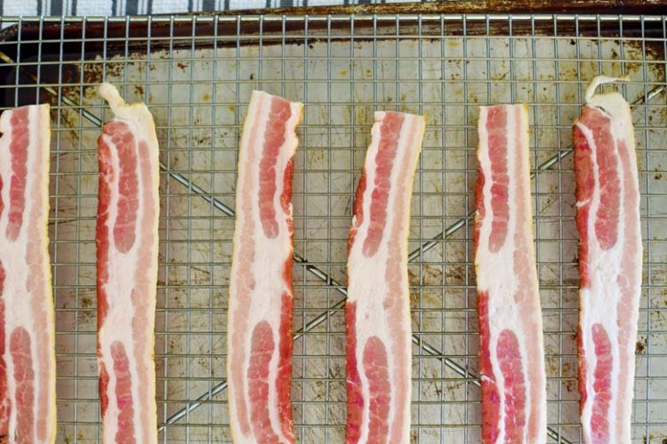 bacon lined up on a rack over a cookie pan about to go in the oven