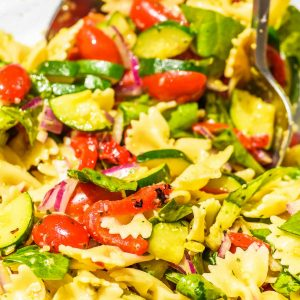 tossing up a bowl of pasta salad with red peppers and artichokes